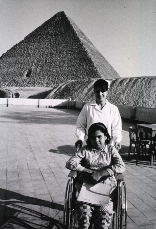 <p>Exterior view: a young girl is sitting in a wheelchair, a nurse-attendant is standing behind her; pyramid in the background.</p>