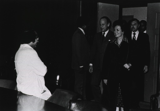 <p>Jihan Sadat, wife of Egyptian Prime Minister Anwar Sadat, is entering a room where Arthur Levine, chief of the National Cancer Insitute's Pediatric Oncology Branch, is leaning against a conference table.  Donald S. Fredrickson, director of the National Institutes of Health (NIH), is to Mrs. Sadat's right.  Several men are entering the room behind them.</p>