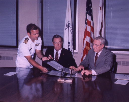 <p>Two men seated at a table exchange copies of documents for signing, a third man, wearing a PHS uniform, helps switch the documents.</p>
