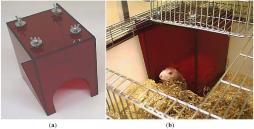 This nest box is designed for rats with external devices. (a) The box has a wide entrance and is bolted to the cage lid so that the animal cannot move it. The corners are extended to meet the side of the cage at the front left and back right of the box to prevent animals from squeezing between the box and cage walls. (b) The adapted box in situ.