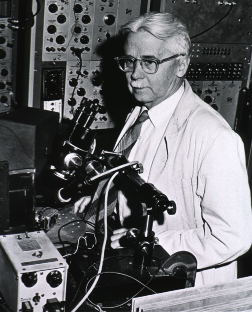 <p>Half-length, left pose; standing in laboratory; wearing white lab coat and glasses.</p>
