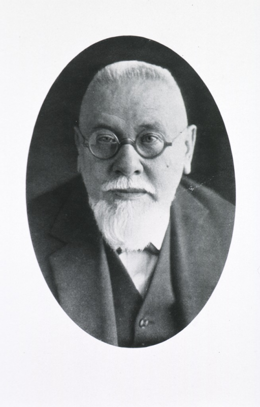 <p>Head and shoulders, full face; wearing glasses; in oval.</p>