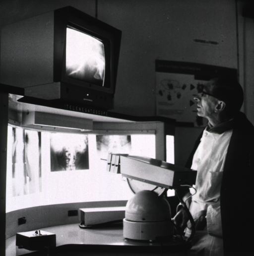 <p>A physician, using a telenegatoscope, is transmitting close-up images from illuminated x-ray film to a large television screen.</p>