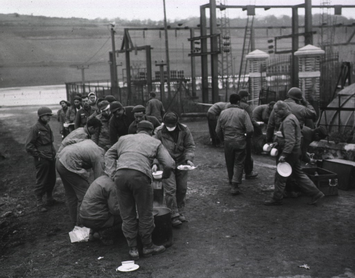 <p>Wounded men stand in a line to get food.  In the background, the rising waters are visible.</p>