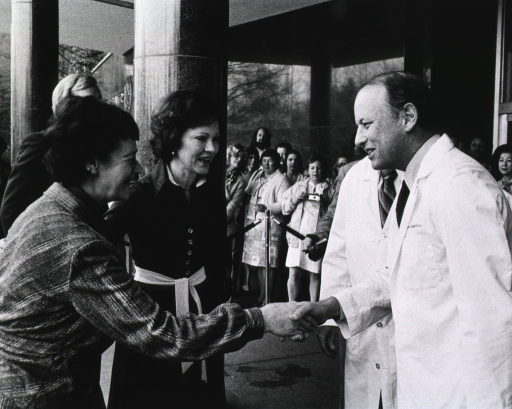 <p>In front of a National Institutes of Health (NIH) building, Dr. Donald S. Fredrickson is shaking hands with the British ambassador's wife.  Rosalyn Carter and a partially visible man in a suit are standing across from Dr. Fredrickson.  Next to Dr. Fredrickson is a partially visible man in a lab coat. There is a crowd of onlookers standing behind a corded-off area.</p>