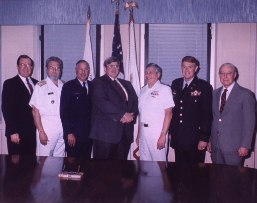 <p>A group of men pose behind a table; all are shown three-quarter length, some wear uniforms.</p>
