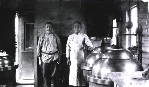 <p>Two men standing in the hospital railroad kitchen car.</p>
