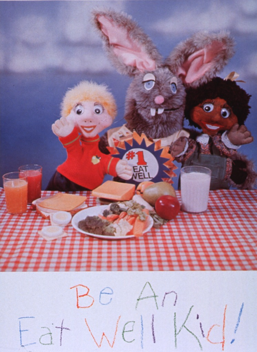 <p>White poster with multicolor lettering.  Top of poster features a reproduction of a color photo.  The photo shows three puppets (two children and a rabbit) standing behind a table laden with nutritious foods including milk, fruits, vegetables, cheese, eggs, and juices.  Title is below photo.  Lettering resembles writing with crayon.</p>