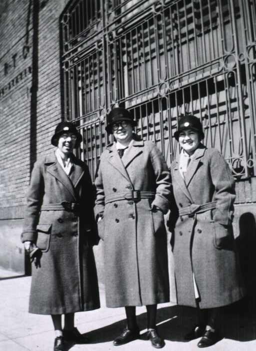 <p>All three women are standing next to a building.</p>