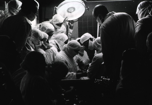 <p>Interior view of a crowded operating room: Prof. de Watterville is being observed by many fellow medical personnel during an operation on the heart.</p>