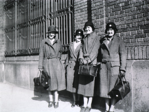 <p>All four women are standing next to a building.</p>