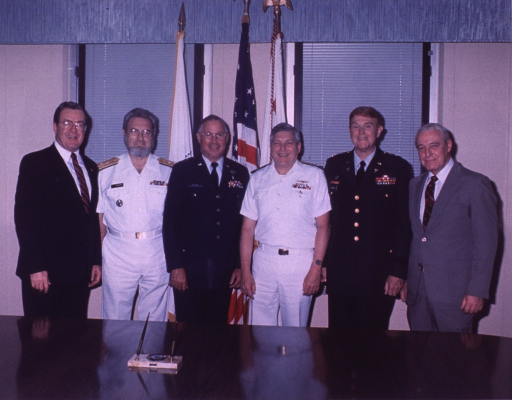 <p>Surgeon General C. Everett Koop and several other men stand behind a table.</p>