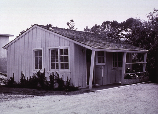 <p>Exterior view: small building with trees in the background; a motorized piece of equipment is on the covered porch; dirt or gravel is the ground cover.</p>