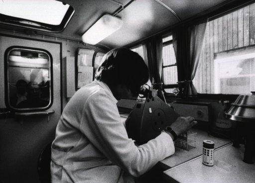 <p>Interior view of the laboratory of a mobile clinic: a technician is analyzing urine(?) samples from patients.</p>