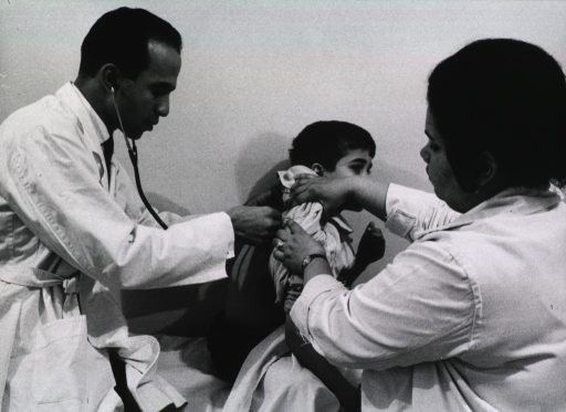 <p>A physician using a stethoscope is examining a young boy. A nurse assists.</p>