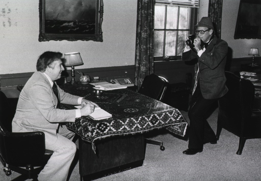 <p>Tom Joy is sitting at a desk in the director's office signing a guest book.  Dr. Donald S. Fredrickson, director of the  National Institutes of Health, is wearing a hat and holding a camera directed toward Tom Joy. There is a cloth over the desk and a painting of an ocean scene on the wall adjacent to the desk.  A wing chair, a desk, a table with a lamp, and a painting on the wall are behind Dr. Fredrickson.</p>