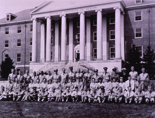 <p>A group photo of the men and women participating in the 16th orientation course; three rows, sitting on the ground, in chairs, and standing at the edge of the lawn in front of Building 1; many in uniform.</p>