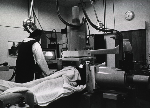 <p>A patient is lying under an x-ray machine and a physician is observing a monitor; x-ray technician is visible through a window to the left.</p>
