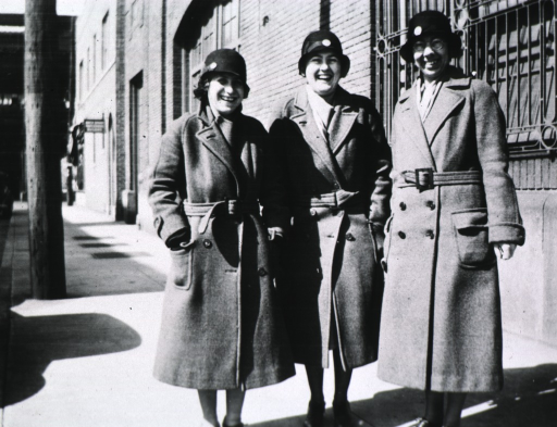 <p>All three women are standing near a building.</p>