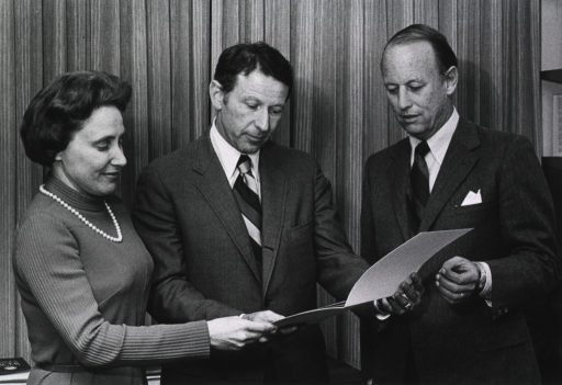 <p>Drs. Ruth Kirschstein, director of the National Institute of General Medical Sciences (NIGMS), Paul Berg, Nobel laureate and professor of biochemistry at Stanford University School of Medicine, and Donald S. Fredrickson, director of the National Institutes of Health (NIH) are standing together looking toward the contents of a white folder.</p>