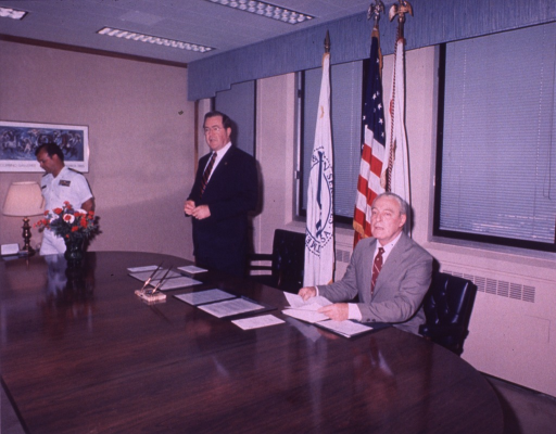 <p>Three men around a table, one is seated, another stands by his chair, and the third, wearing a PHS uniform, is walking away; on the table are copies of documents to be signed.</p>