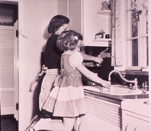 <p>Child kneeling on a stool is rinsing cans at the kitchen sink.</p>