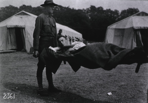 <p>A patient is being transported on a stretcher; in the background are two tents, part of Red Cross Mobile Hospital Number 5 which was set up on a former race track at Auteuil, France.</p>