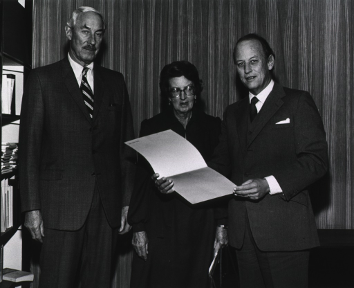 <p>John Eberhardt, Mary Leakey, and Donald S. Fredrickson are standing together.  Dr. Fredrickson is holding an open white folder.</p>
