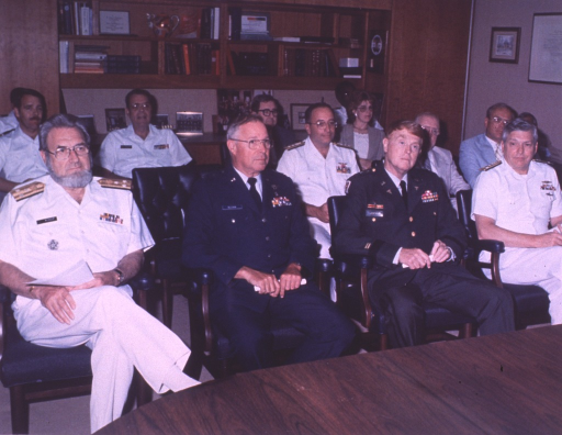 <p>Several men and a woman sit in chairs arranged in rows in an office.</p>