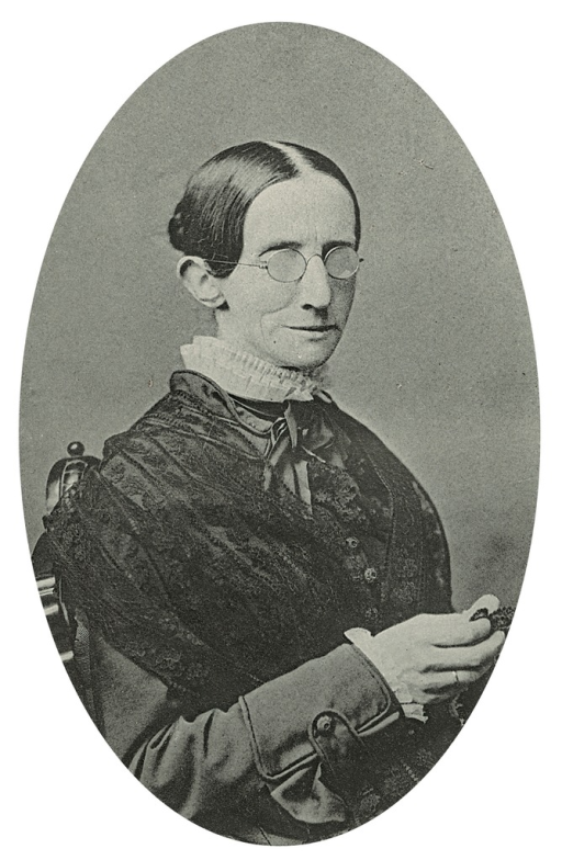 <p>Image of a black and white photograph of Laura Bridgman in her late forties, engaged in crochet work which she sold to visitors for pocket money. Her hair, parted in the middle, is arranged in a tight bun, and she is wearing glasses. She is dressed in a long-sleeved dress with a high collar. Life and education of Laura Dewey Bridgman, fronspiece.</p>
