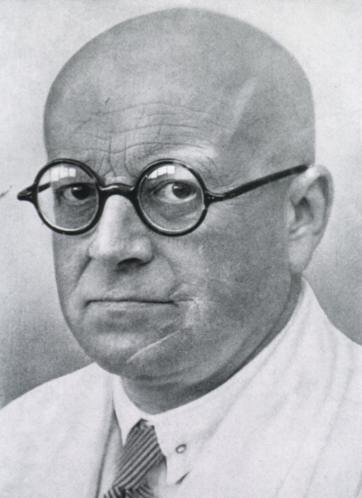 <p>Head and shoulders, left pose, full face; black rimmed glasses, bald head, heavy lines in forehead.</p>