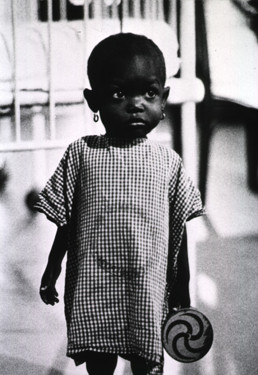 <p>A little girl shown standing, three-quarter length; she is holding a toy, a crib is in the background.</p>
