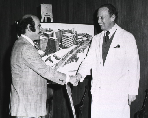 <p>Dr. Donald S. Fredrickson, director of the National Institutes of Health (NIH), is shaking hands with Congressman Henry A. Waxman, 29th district of California.  Behind them, on an easle, is a drawing of a building complex.  On the lower right hand corner it reads: ambulatory care research, the National Institutes of Health.  Dr. Fredrickson is in a lab coat.</p>