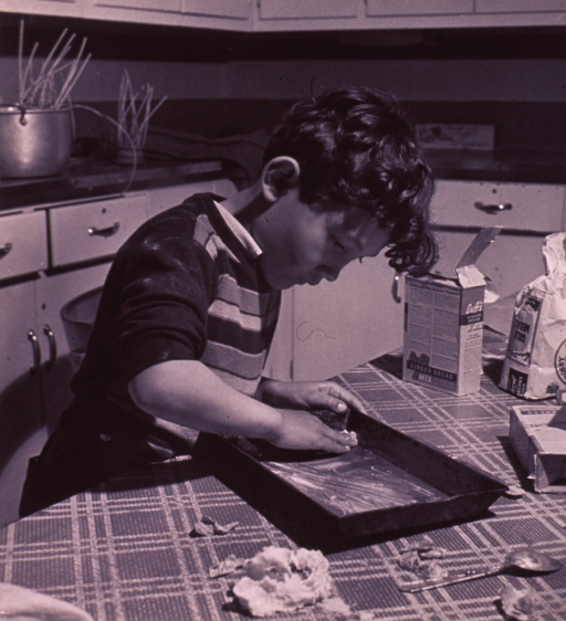 <p>A &quot;Boys' Club&quot; member is greasing a pan in which to bake gingerbread men.</p>