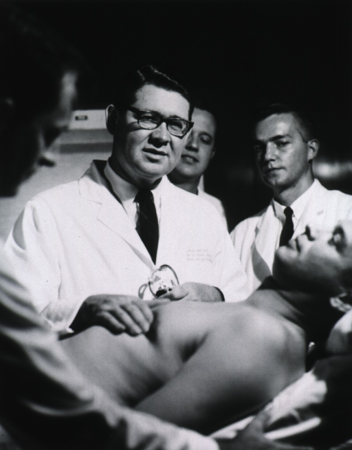 <p>Half length, full face; wearing glasses and lab coat; palpating patient's chest as others (students and interns?) watch.</p>
