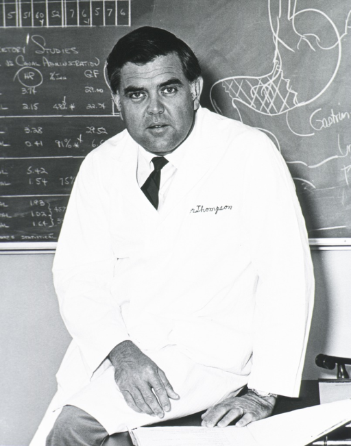 <p>Three quarter length, full face; wearing lab coat; beside desk, in front of blackboard which has a drawing of the stomach.</p>