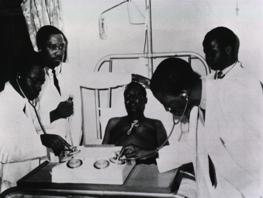 <p>A patient is connected to the multi-channeled stethoscope; four students are standing around his bed, two of them are holding their stethoscopes to the device through which they are listening to the patient's heart.</p>