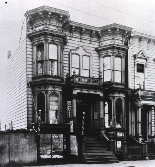 <p>View of front and side of a rowhouse in San Francisco's Chinatown with storefront signs in English and Chinese advertising a barber shop and a laundry during the San Francisco plague campaign.</p>