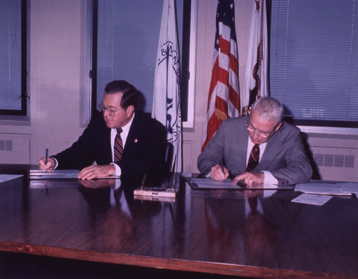<p>Two men seated at a table signing copies of a document.</p>