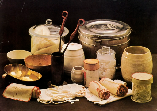 <p>Poster shows glass, ceramic, and metal containers along with a rolled cloth surround a long-handled instrument in a flat base cylinder. The glass containers contain fabric which may be bandaging material.</p>