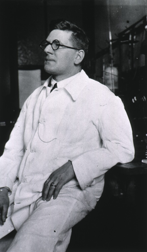 <p>Three-quarter length, left pose, seated in laboratory wearing white coat.</p>
