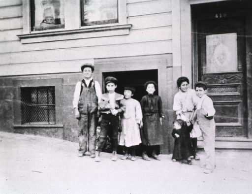 <p>Group portrait of seven children standing in front of a building and doorway during the San Francisco plague campaign.</p>