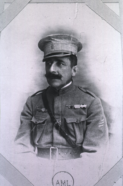<p>Seated, wearing army uniform and cap.</p>