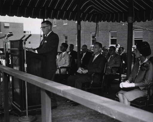 <p>View of podium showing King and Queen of Thailand, Surgeon General Leroy Burney, and Dr. Roderick Murray.</p>