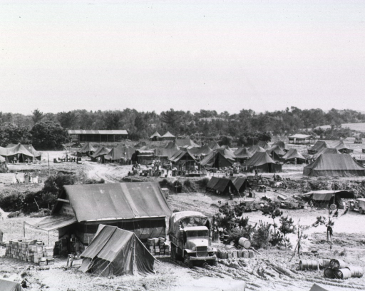<p>Tents are pitched on a grassless terrain.  Supply trucks are parked next to some of the tents.  A few servicemen are seen walking.</p>