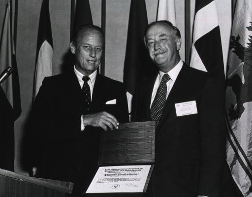 <p>Dr. Donald S. Fredrickson, director of the National Institutes of Health (NIH) is standing with Dr. James   Stengle, formerly of National Library of Medicine's (NLM) Lister Hill Center.  Dr. Fredrickson is holding a certificate of appreciation for his address on June 26, 1977 at the opening ceremony of the congress held in Philadelphia.  Dr. Fredrickson is standing slightly to the side and behind a podium with a mircophone.  In the background there are flags.</p>