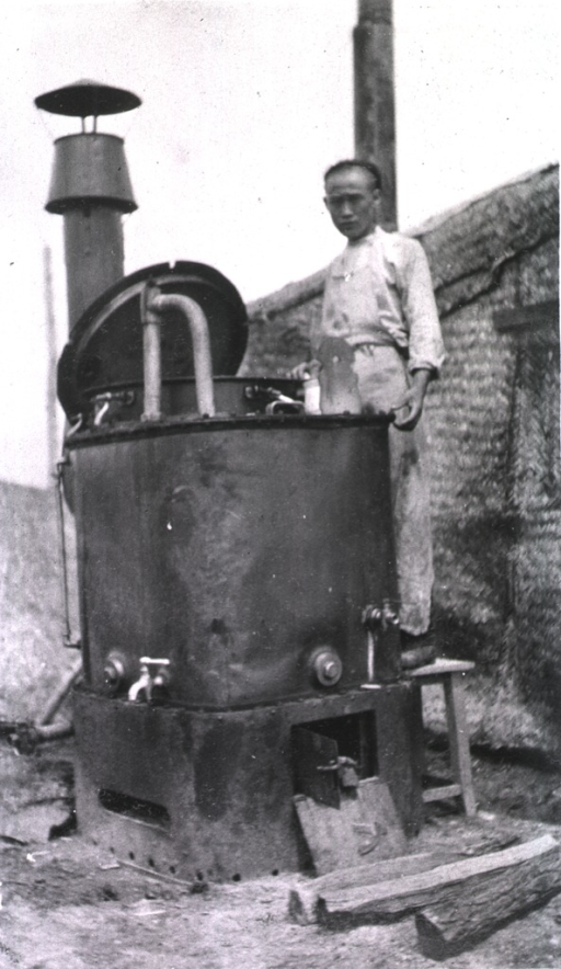 <p>A servant stands beside a soup boiler at Vetebsk Red Cross Hospital.</p>