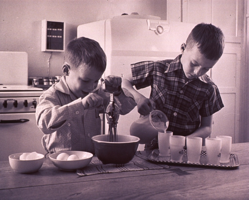 <p>Two brothers are helping prepare breakfast.</p>