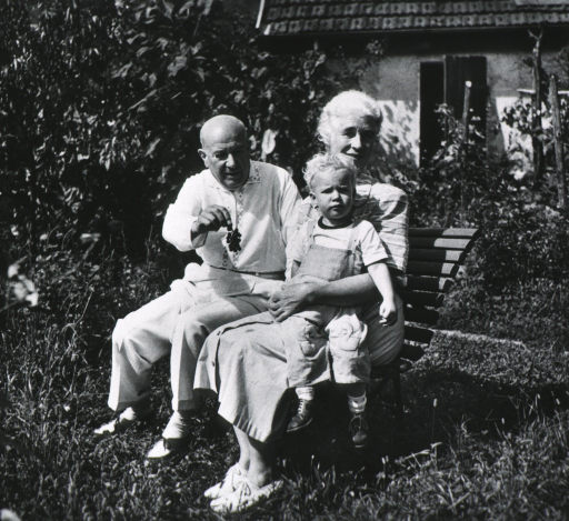 <p>Full length, seated on bench in garden with his wife, Emmy, who is holding child on her lap.</p>