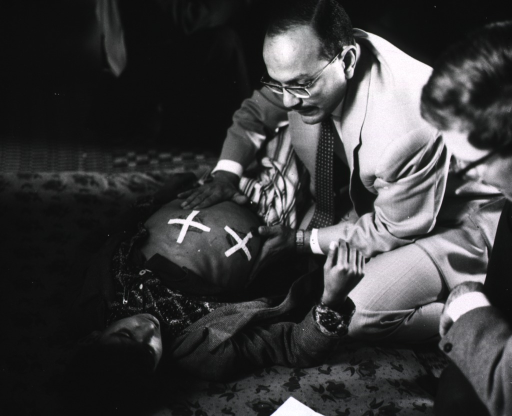 <p>A young boy lying on a mat on the floor is being examined by a physician; vine leaves covering cauterization scars on his chest are testament to the treatment by quack physicians.</p>